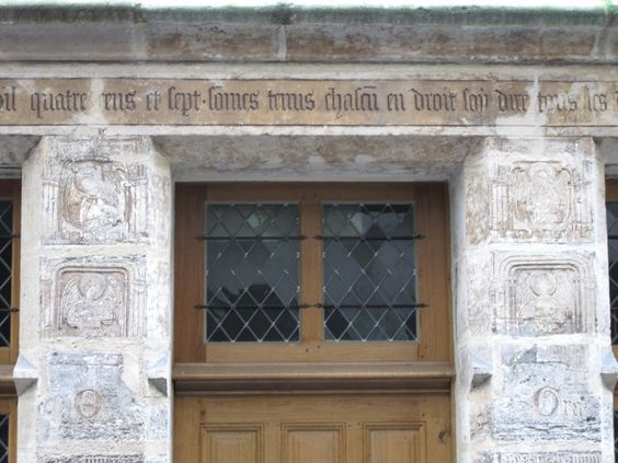 The inscription above the door at Flamel's house, flanked by musician angels