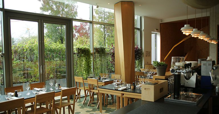 The bright, modern lower dining area at Coretta features light wood and airy architectural elements. The outside terrace area is also very pleasant. Image credit: Miamidees.com