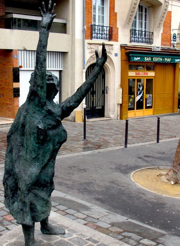 "This contemporary statue representing ""the little bird"" is situated on Place Edith Piaf in Paris, with a bar in her honor just behind it. Image credit:"