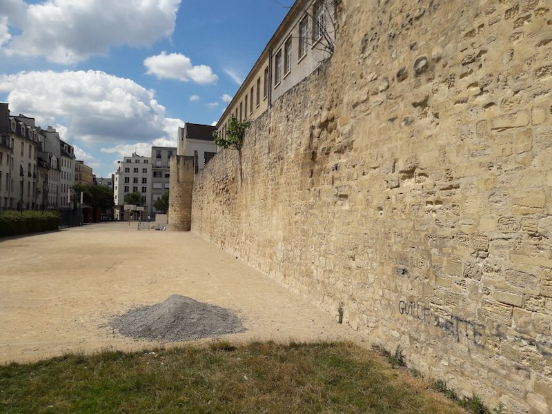 "Part of the old fortified wall that surrounded Paris under King Louis Philippe is visible on Rue des Jardins St Paul in Paris. Image: <a href= ""http://www.unjourdeplusaparis.com/en/paris-insolite/enceinte-philippe-auguste-rue-jardins-saint-paul"" srcset="