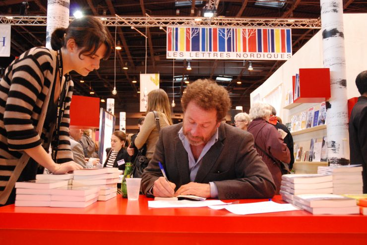 An author signs a book for a reader at the Salon du Livre in Paris (Paris Book Fair)