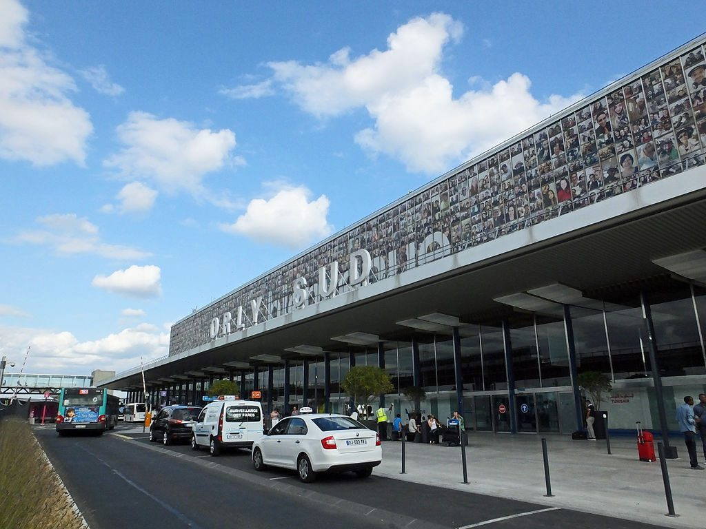 "A taxi waits outside Paris' Orly Airport, South Terminal. Always find the official taxi queue and look for an illuminated ""taxi"" sign on the rooftop of the car."