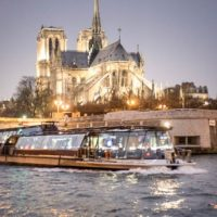 Bateaux Parisiens dinner cruise on the Seine, with Notre Dame Cathedral in the background.