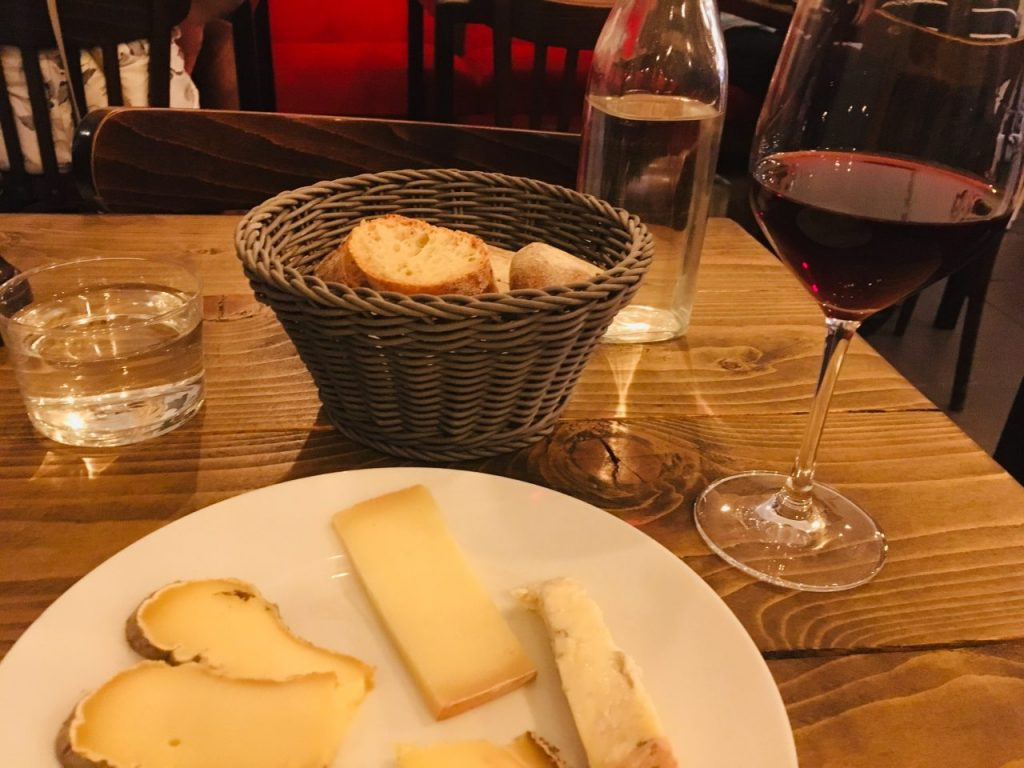 A cheese plate accompanied by a glass of red at Le Flacon, Bordeaux. Image credit: Courtney Traub/All rights reserved