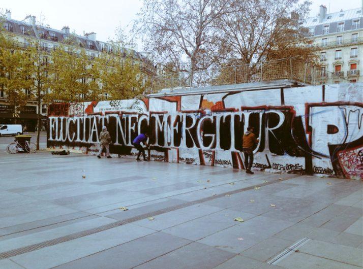 """Street artists paint """"Fluctuat nec mergitur"""" on a wall on Place de la République, following the November 2015 terrorist attacks in Paris."""